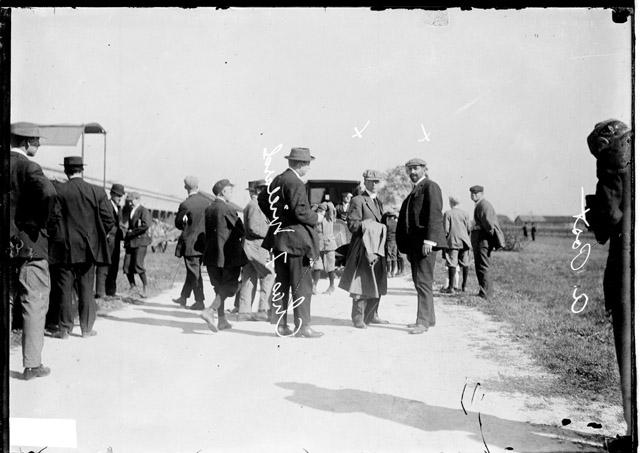 [Charles F. Willard, Augustus Post and an unidentified man standing in a lane at the Hawthorne race track with a group of men standing nearby]