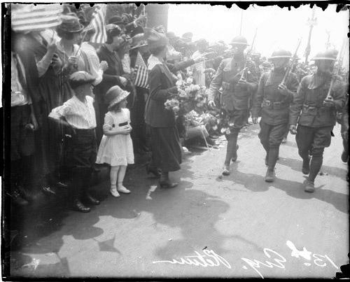 [13th Engineers Division, woman handing flowers to soldiers marching upon their return home]