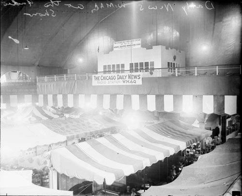 [Banner advertising Chicago Daily News radio station WMAQ hanging above tents in a large auditorium or convention space]