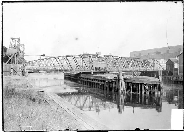 [Old Archer Avenue swing bridge, side view with commercial or industrial buildings visible in the background]