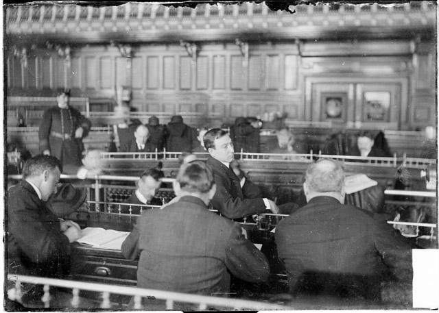 [Albert A. Memhard, seen in three-quarter profile, testifying before the speaker's rostrum in the council chamber during the Iroquois Theater fire investigation]