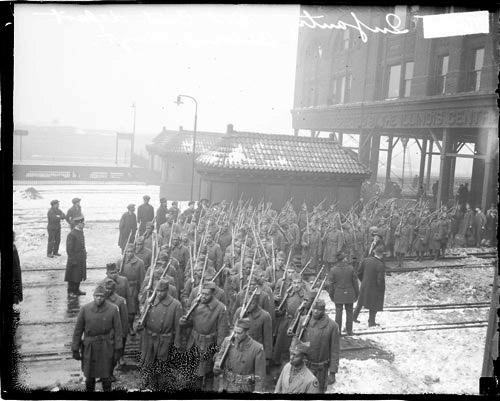 [365th Infantry, African American infantry, marching with rifles at Illinois Central Railroad Station]