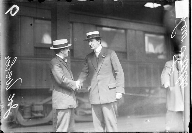 [Actor Joe Weber and Lew Fields, vaudeveille comedians, standing next to a train car, shaking hands]