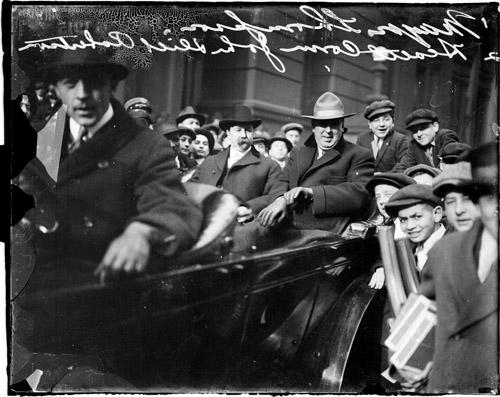 [Health Commissioner, Dr. John Dill Robertson, and Mayor William Hale Thompson, riding in an automobile during a parade]