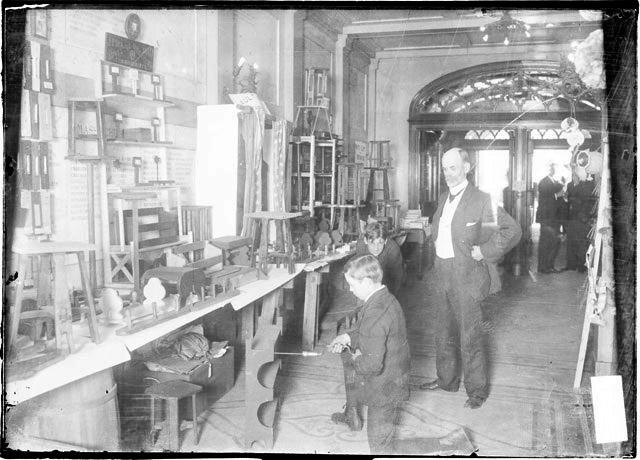 [Carpenter class at the Chicago Boys Club, one boy drilling while another boy and a teacher watch]
