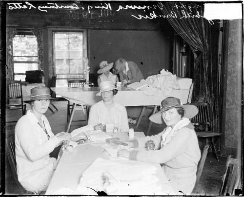 [Gineva King, Courtney Letts, and Elizabeth Brockie, sitting around a table, rolling bandages]