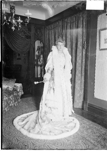 [Lucille Nau, queen of the 1904 Madison Street Merchants Carnival, standing, wearing a gown and cape and holding a scepter]