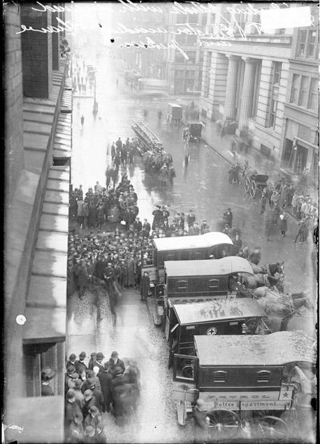 [Ambulances backed against a sidewalk to receive people injured in an elevator accident that took place in a building at South Wells Street and West Jackson Boulevard]