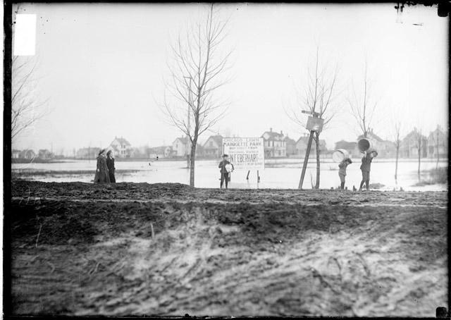 [Boys carrying empty barrels on their shoulders near Marquette Park which is covered with flood waters]