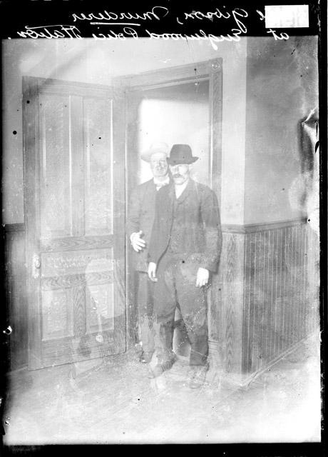 [Cecil Gibson, accused murderer, standing in a doorway in the Englewood police station with a policeman standing behind him]