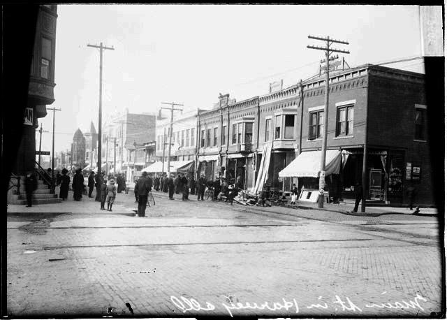 [People standing in Main Street in Harvey, Illinois, outside a partially burnt building, view from a cross street]