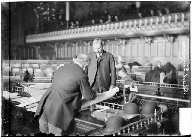 [Edward Laughlin standing before a large stack of papers on the speaker's rostrum in the council chamber during the Iroquois Theater fire investigation]