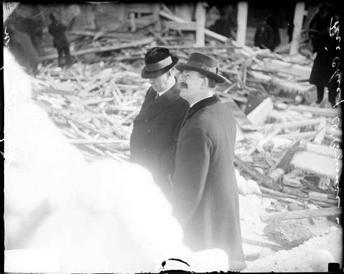 [Mayor William Hale Thompson, standing with Fire Chief Thomas O'Connor, amidst the debris left after a tenement building explosion]