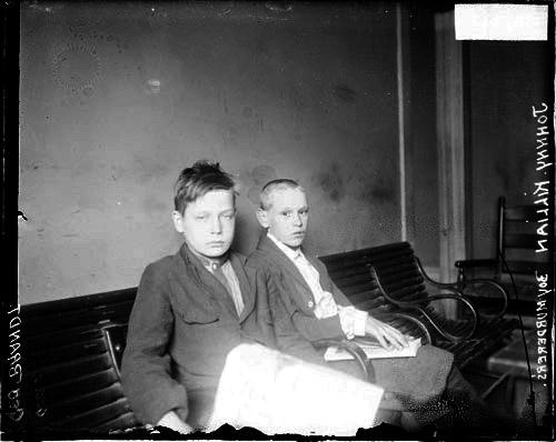 [Accused boy murderers, George Brandt and Johnny Killian, sitting on a bench in a hallway, from the left]