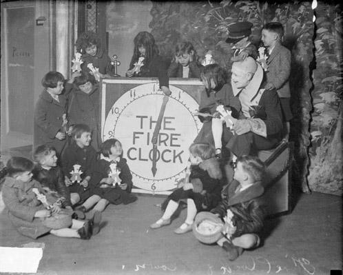 [Clown sitting with a group of children in a room next to a large clock]