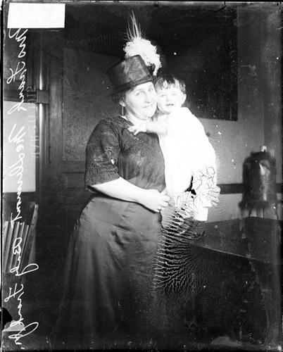 [Anna McDermott, standing in a room, holding her infant son Frank McDermott, Jr.]
