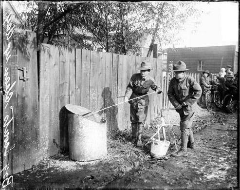 [Clean Up Day, Near South Side, Boy Scouts whitewashing a metal barrel]