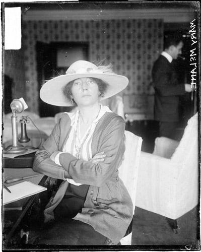 [Author, Mary McLane, sitting with her arms crossed at a desk in a hotel room]