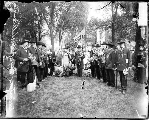 [Veterans holding bouquets of flowers, standing in front of a flag draped memorial at Rosehill Cemetery during a Memorial Day celebration]