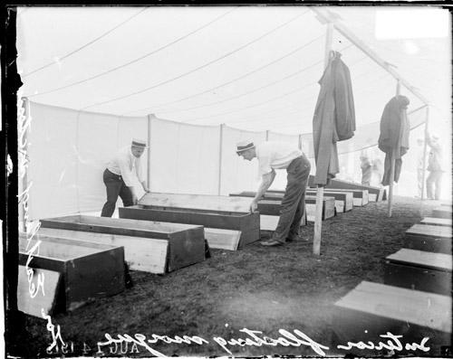 [Eastland disaster, interior of floating morgue, two men handling a coffin lid]