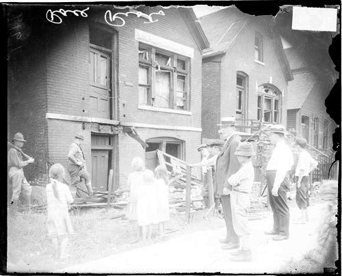 [Chicago race riot, white men, boys and young girls standing in front vandalized house]