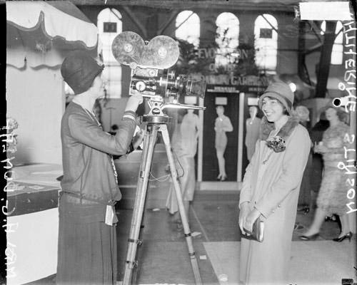 [Katherine Stinson, aviator, standing in front of a motion picture camera with Mrs. A. G. Dunlap standing behind the camera]
