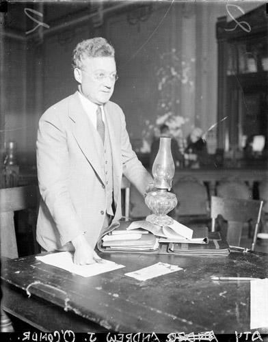 [Andrew J. O'Connor holding a candle lamp, standing at a desk in a courtroom]