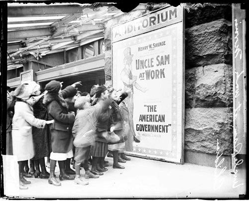 [Children pointing at movie poster for Uncle Sam at Work at the Auditorium Theater, close up]