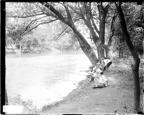 [Boys sitting and fishing in a forest preserve on the bank of the Des Plaines River]