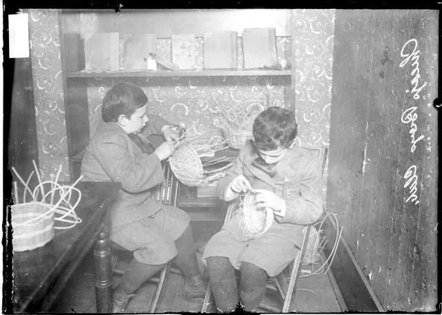 [Two boys, members of the Chicago Boys Club, wearing suits, weaving baskets]