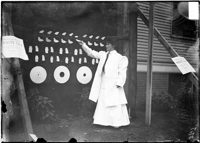[Mrs. James McLurdy in front of a structure strung with small animal figures at White City amusement park]