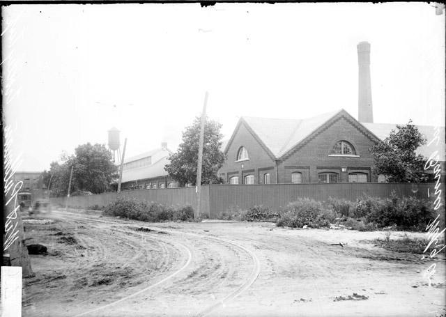 [Whitman & Barnes Manufacturing Company building, in Pullman Town, view across a turn in the road toward a turn in the enclosing fence]