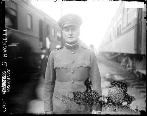 [Colonel Horatio B. Hackett, 124th Field Artillery, U. S. Army, Camp standing between two trains]