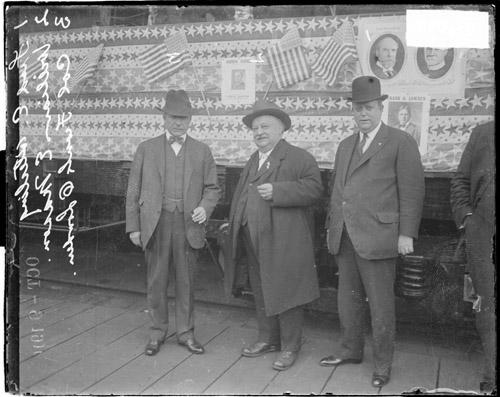 [Frank Lowden, Illinois Republican Senator William Mason, and Fred Sterling, standing in front of a decorated traincar]