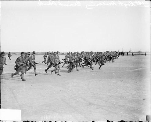 [131st Infantry carrying rifles and running across a field at Grant Park]