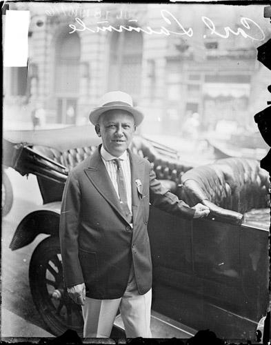 [Carl Laemmle, standing by an automobile on a street]