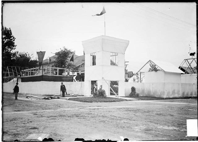 [White City amusement park, fence and entrance tower under construction with two men (one a policeman) standing nearby]