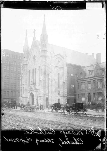 [St. Mary's Catholic Church with horse-drawn carriages driving along the street and men standing on the sidewalk in front of the church]