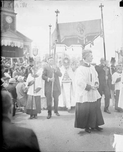 [Eucharistic Congress in Mundelein, Illinois, with clergyman walking in front of a canopy in a procession and church visible on the left]