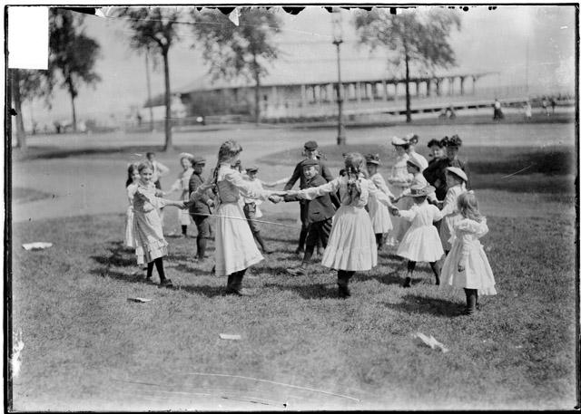 [Children playing a circle game on a slope of grass with the Chicago Daily News Sanitarium in the background across Lake Shore Drive]