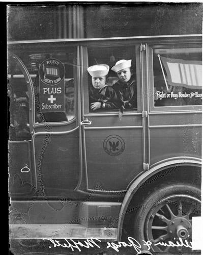 [William Adger Moffett's children, George and William, leaning out window of automobile advertising liberty bonds]