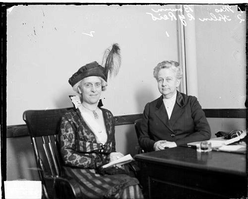 [Illinois State Council of Defense member, Mrs. Joseph Bowen, and Helen Reid, sitting at a desk together, both looking at the camera]