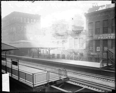 [Elevated railroad station at East Madison Boulevard and Wells Street (formerly Fifth Avenue), viewed at an angle across the station from slightly above the platforms and tracks and including nearby buildings in the background]