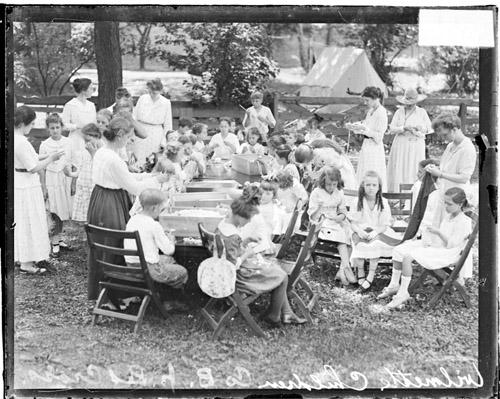 [Junior Red Cross, Company B, children and adults, knitting at tables set up outdoors in Wilmette]