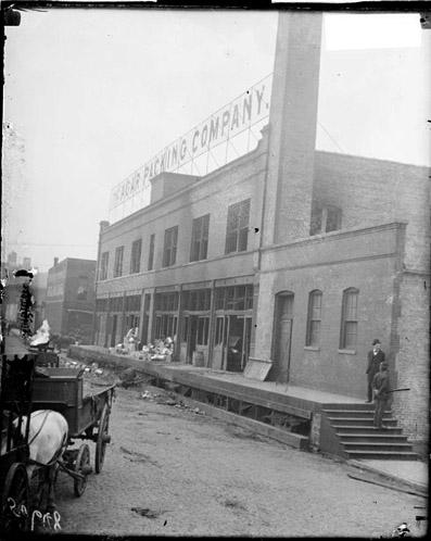 [Agar Packing Co., view of loading dock with piles of things on it and two men standing on one side near the stairs ]