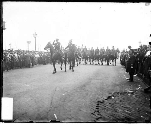 [Prosperity parade, two uniformed policemen leading a line of mounted police past spectators lining both sides of the street]