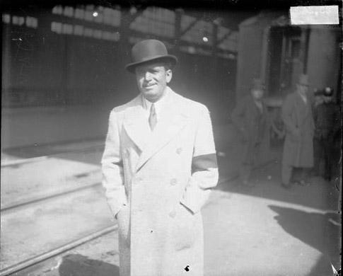 [Actor Douglas Fairbanks standing outside on a train platform at a railroad station]