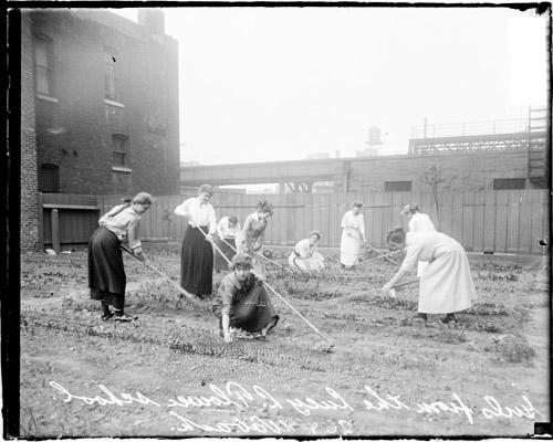 [Girls gardening in the fenced grounds of the Flower Technical School]