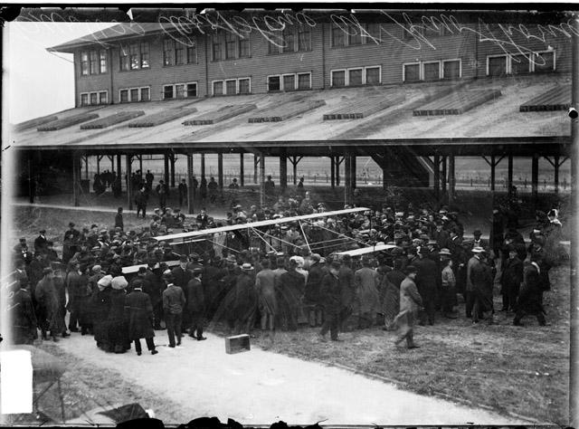 [Crowd on both sides of aviator Glenn Curtiss' biplane at Hawthorne Race Track, view from behind the backs of people in the crowd]