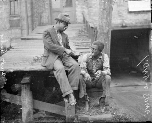 [Actors Charles J. Correll and Freeman F. Gosden from the Amos 'n Andy show, wearing blackface, sitting on a raised wooden walkway in front of a building]